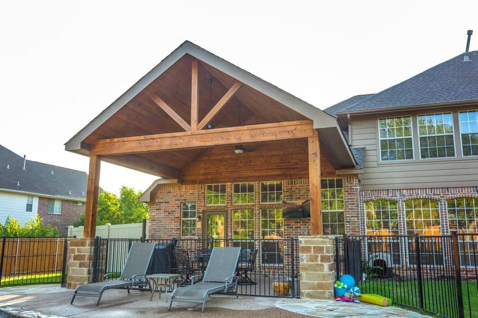 outdoor living spaces - wood patio cover next to pool and pool chairs
