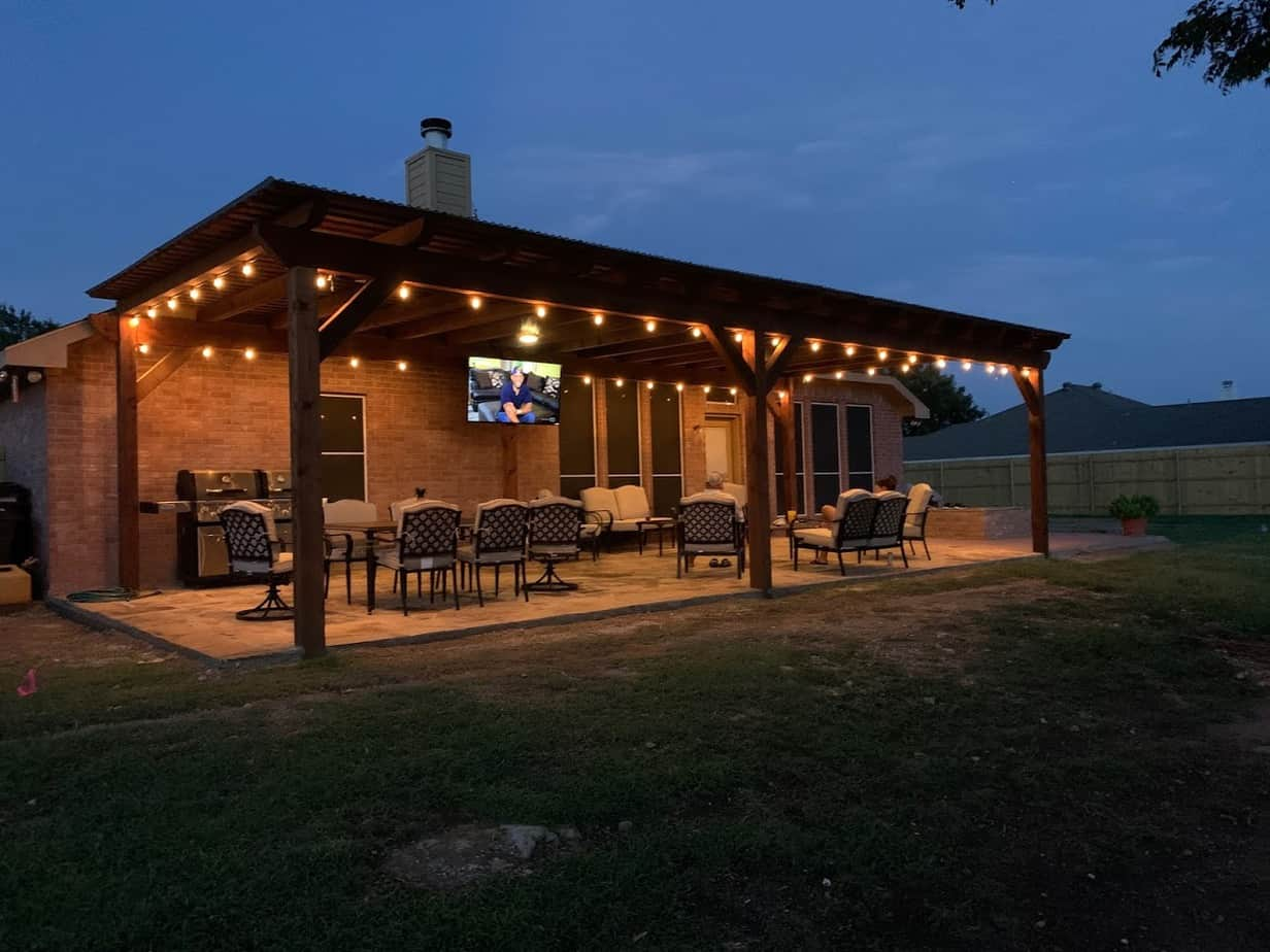 outdoor living - patio cover at night with hanging lights, seating and entertainment